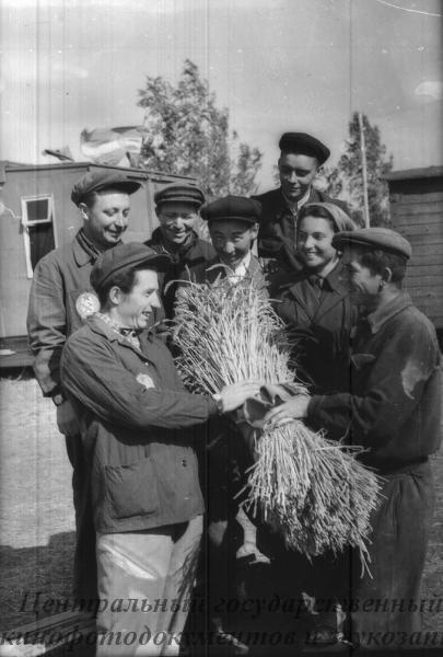 """Группа работников совхоза """"Урнекский"""" вручают сноп комбайнерам венгерской сельскохозяйственной бригады Ференцу Хорварду и Дьердю Картали (справа двое)."""