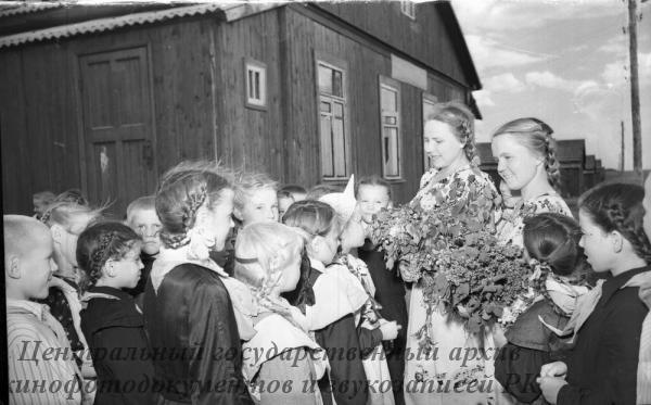 """В школе зерносовхоза """"Урнек"""" закончился учебный год. Дети прощаются со своими учетелями Н. П. Кисенкова (слева) и Н. Ф. Фаектистова."""
